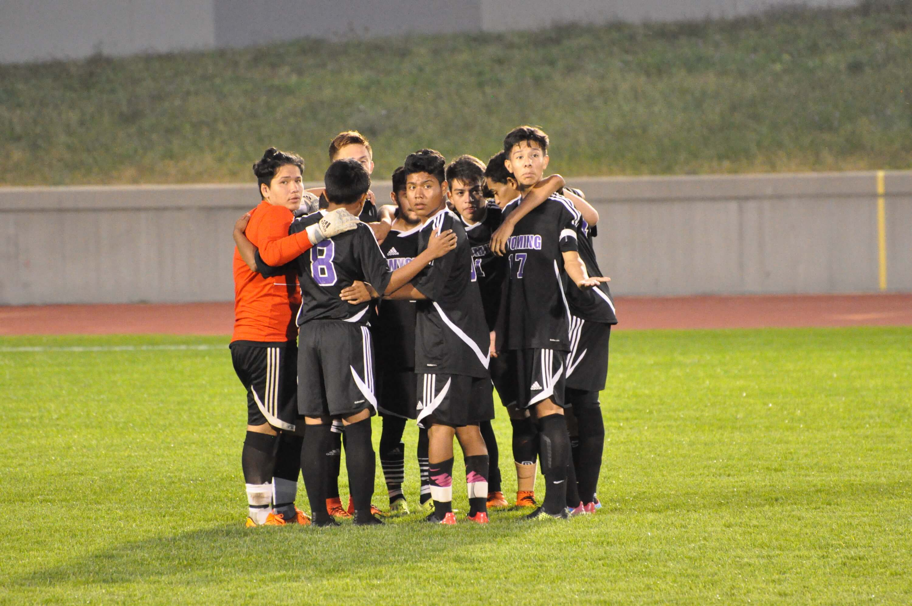 Photo of the soccer team huddle on the field