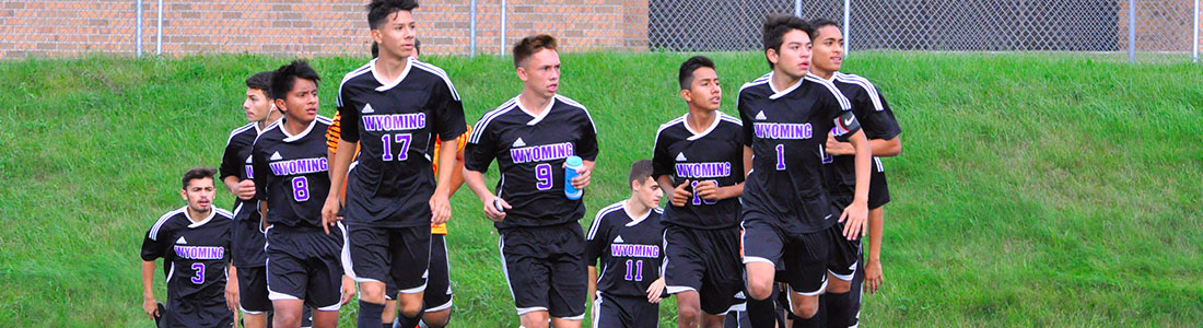 Photo of boys soccer team walking onto playing field.