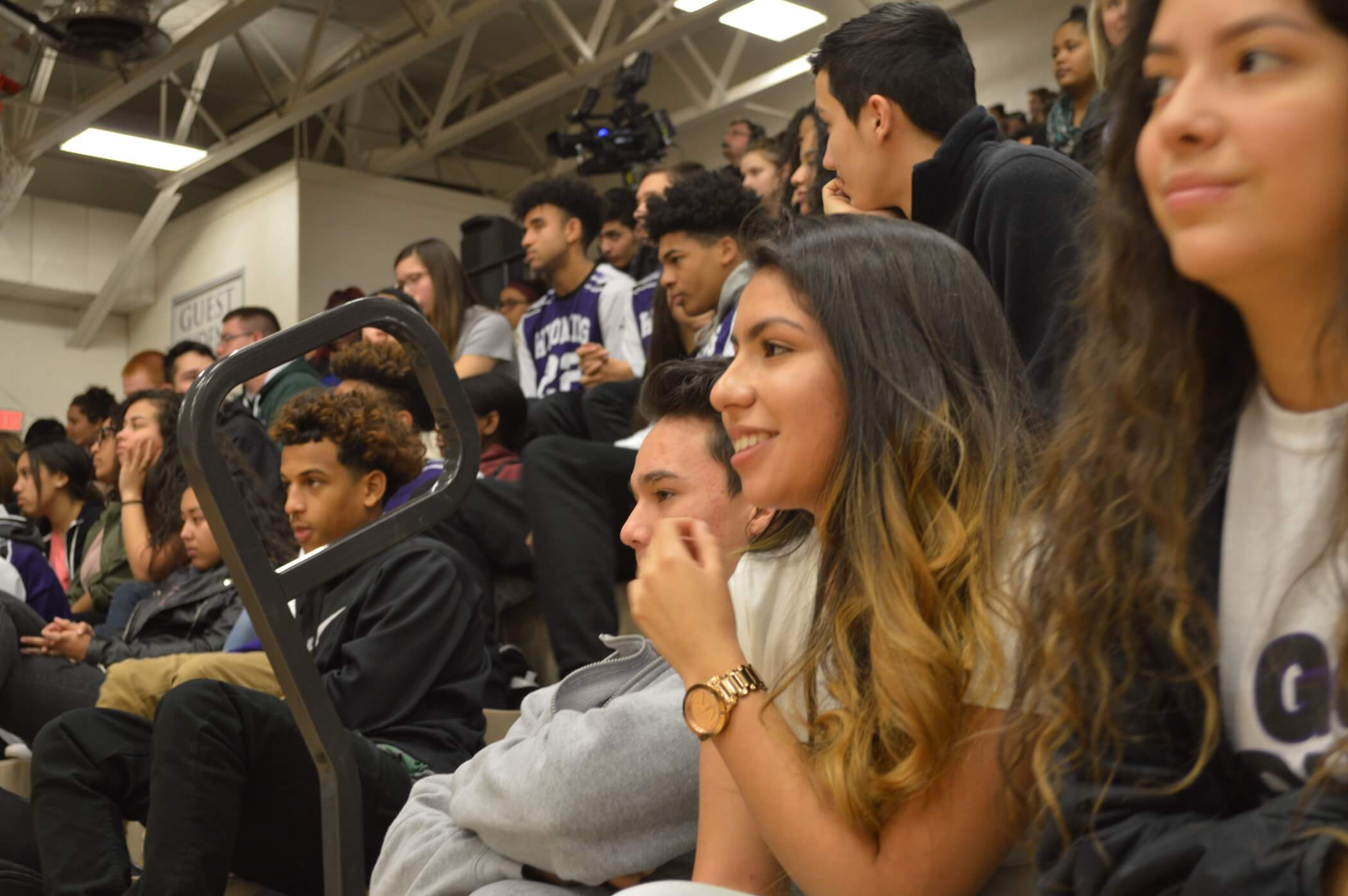 Photo of students sitting on bleachers inside gymnasium attending an assembly.