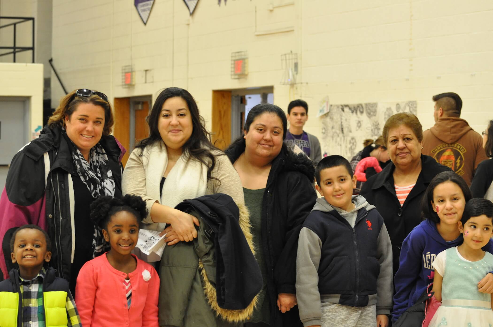 Photo of a student and their family inside a gymnasium.